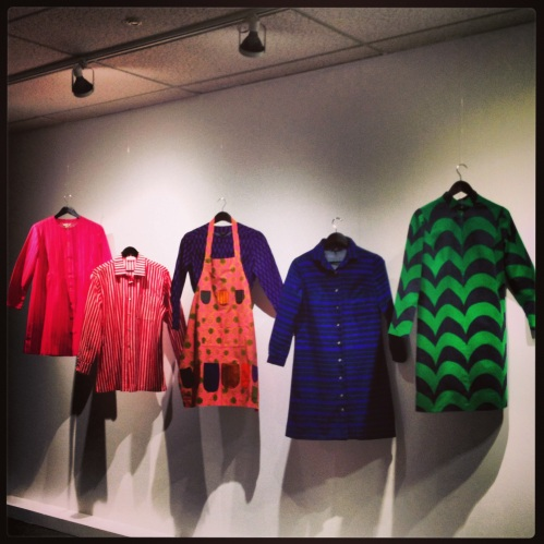 Samples of clothing beginning with the Juolukko (bilberry) dress on the left (1962) and ending with a dress in the 'Oasis' pattern from 1967 by Annika Rimala.  The jokopoika shirt is second from the left.