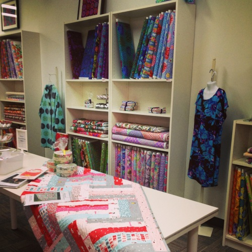 A view into the shop showing the Westminster Fabrics on the shelves, and two garments from the Amy Butler trunk show.The turquoise coat is actually cotton velvet which the shop also sells off the bolt. Beautiful!