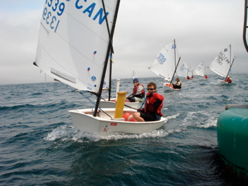 A photo depicting my son crossing the finish line in an Optimist Dinghy (some years ago).